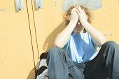 stock photo of playground school  - sad lonely boy in the school playground - JPG
