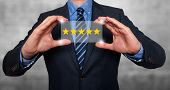 Businessman holding five star rating - Stock Image