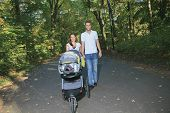 A smiling couple with baby stroller in a park