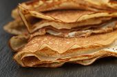 thin crepes or blinis folded in triangles on slate board