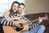 foto of serenade  - A Handsome man serenading his girlfriend with guitar at home in the living room - JPG