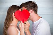 Side view of romantic couple holding heart against bleached wooden planks background