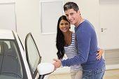 Couple holding a car door handles at new car showroom
