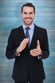 Happy businessman standing and applauding against wooden planks