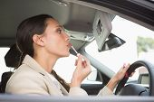 Businesswoman using mirror to put on lip gloss in her car