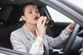 Woman drinking beer while driving in her car