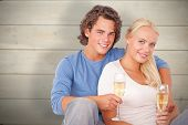 Couple with glasses of sparkling wine against bleached wooden planks background