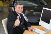 Smiling businessman giving thumbs up at his desk at new car showroom