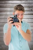 Handsome young man holding digital camera against wooden planks