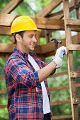 Smiling male worker using hammer in wooden cabin at construction site