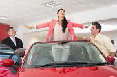 Woman having fun in her new red convertible at new car showroom