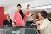 Woman standing in red cabriolet and man taking picture at new car showroom