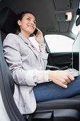Businesswoman working in the drivers seat in her car