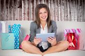 Beautiful woman on sofa with a tablet and credit card against wooden planks