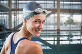 Pretty swimmer by the pool smiling at camera against empty swimming pool with lane markers
