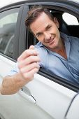 Handsome man smiling and holding key in his car