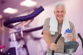 Senior man on exercise bike against row of exercise bikes focus on foreground