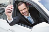 Businessman smiling and showing key in his car