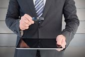 Businessman looking at tablet with magnifying glass against painted blue wooden planks