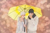 Couple in winter fashion sneezing under umbrella against light glowing dots design pattern