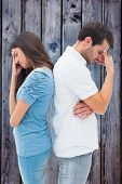 Upset couple not talking to each other after fight against grey wooden planks