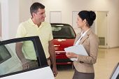 Businesswoman speaking with her customer at new car showroom