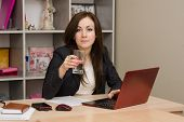 Business Woman At The Computer Holding A Glass Of Water
