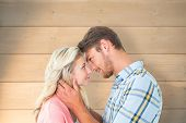 Attractive couple smiling at each other against bleached wooden planks background