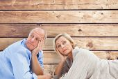 Mature couple lying and thinking against wooden planks background