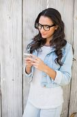 Pretty hipster sending a text against bleached wooden fence