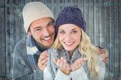 Attractive couple in winter fashion smiling at camera against blue abstract light spot design