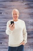 Happy mature man sending a text against faded grey wooden planks