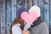 Couple in warm clothing holding heart against wooden background in blue