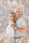 Happy couple smiling at camera against light glowing dots design pattern