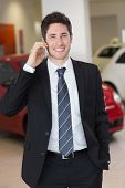 Smiling businessman calling with his mobile phone at new car showroom