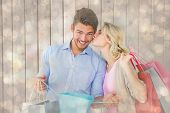 Attractive young couple holding shopping bags against light glowing dots design pattern