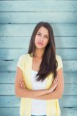 Frowning casual woman looking at camera against wooden planks