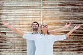 Cute couple standing with arms out against wooden planks