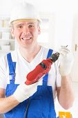 Smiling man with electric drill wearing protective helmet