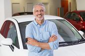 Smiling customer standing with arms crossed at new car showroom