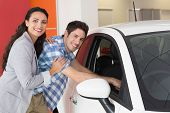 Smiling couple looking inside a car at new car showroom