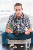 Unsmiling man with a beer and his pills at home in the living room