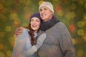 Couple in warm clothing embracing against close up of christmas lights