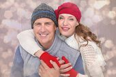 Happy couple in warm clothing against light glowing dots design pattern