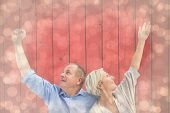 Happy mature couple with hands up against light glowing dots design pattern