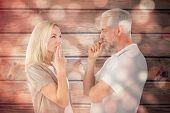 Couple staying silent with fingers on lips against light circles on black background