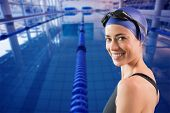 Fit swimmer standing by the pool smiling at camera against empty swimming pool with lane markers