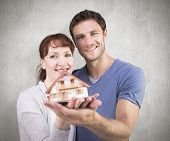 Couple holding a model house against weathered surface