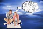 Attractive young couple sitting looking at blueprint against blue sky with blue clouds