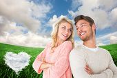 Attractive couple smiling with arms crossed against cloud heart